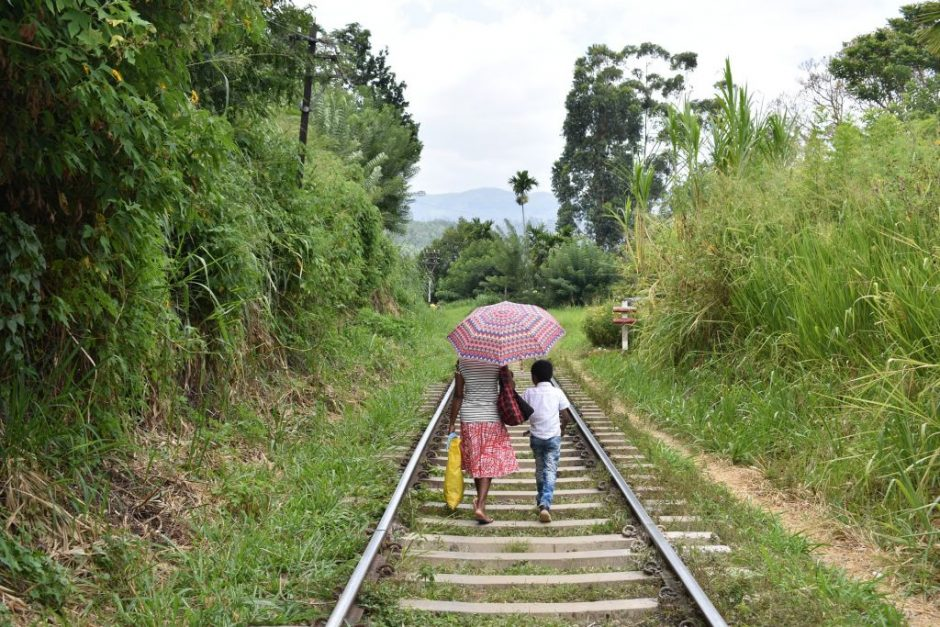 Two Sri Lankan people walking along a train track with their backs to us, one holding a sun parasol / umbrella