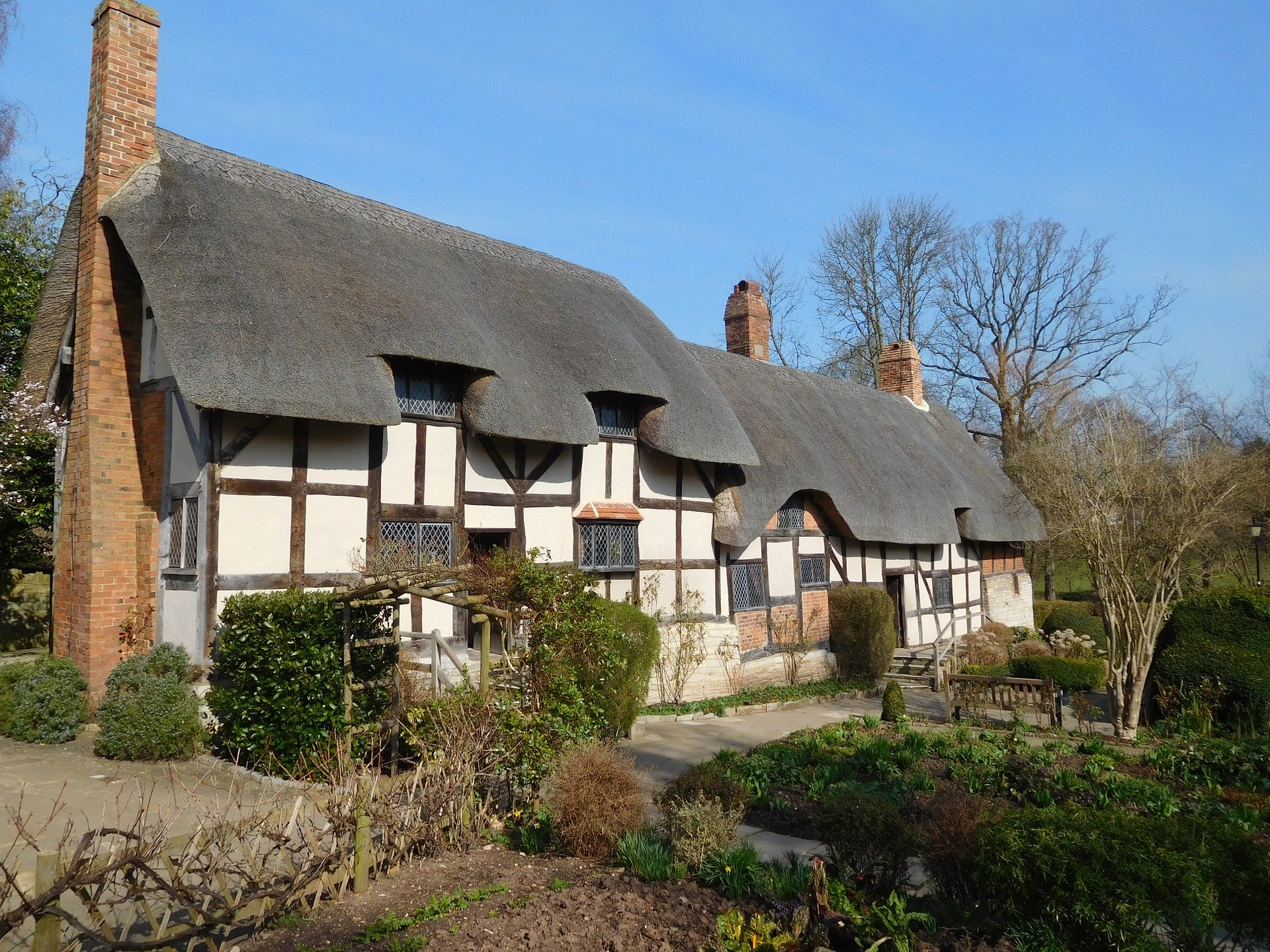 thatched roof cottage suurounded by garden